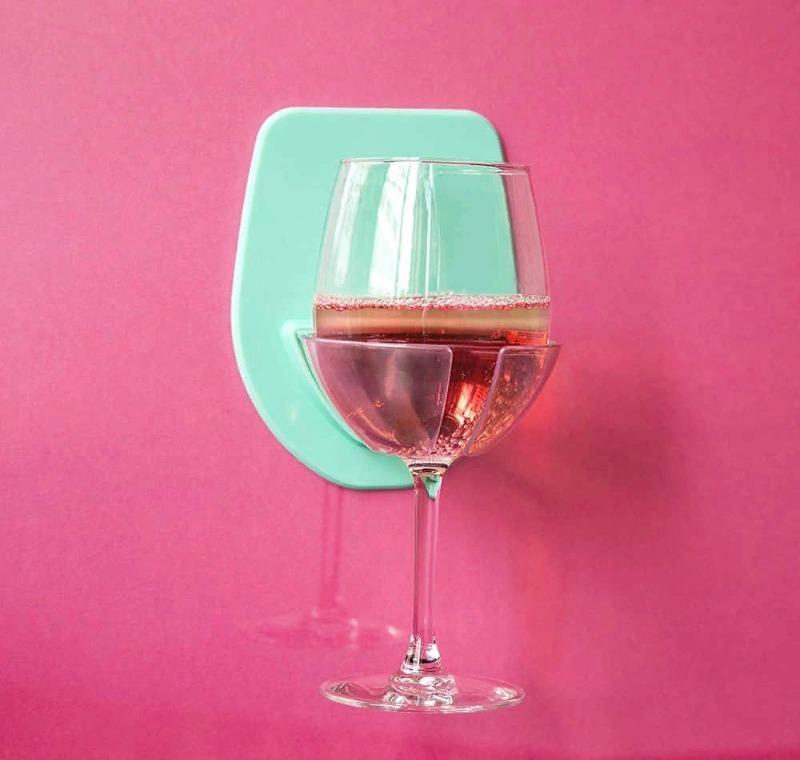 Бокал в держателе на розовой стене